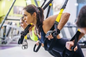 Women doing push ups training arms with trx fitness straps in the gym Concept workout healthy lifestyle sport